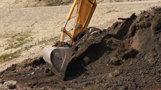 Excavator Scoops Dirt Into Dump Truck
