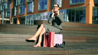 Excited businesswoman chatting on cellphone about her shopping
