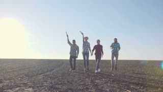 Excited group of four teenagers in empty cultivated field under the blue sky jumping