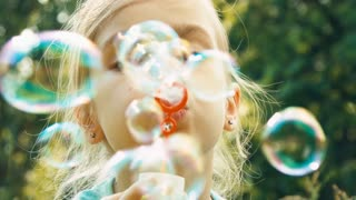 Extreme closeup portrait girl blowing soap bubbles in the grass and smiling at camera. The fountain of bubbles