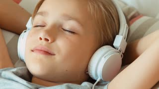 Extreme closeup portrait girl child listening music in headphones with eyes closed and lying on the bed