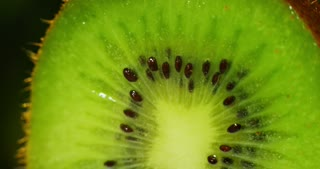 extreme macro of green kiwi dropping fresh water