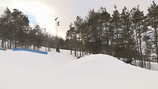 Extreme snowboarder does a backflip barrel roll