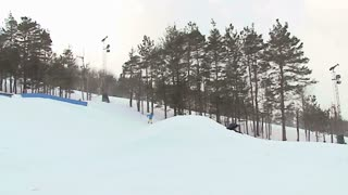 Extreme snowboarder throws a backflip off a jump