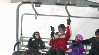 Family Gets Settled On Chairlift, Skiiers In Back