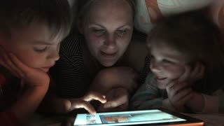Family of three enjoying tablet under blanket