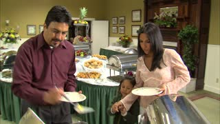 Family Puts Food on Plates at Buffet Table 12