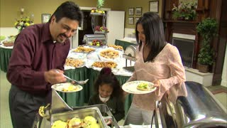 Family Puts Food on Plates at Buffet Table 13