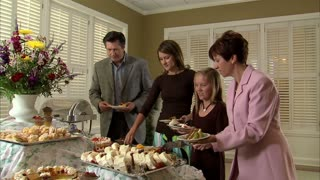 Family Puts Food on Plates at Buffet Table 4
