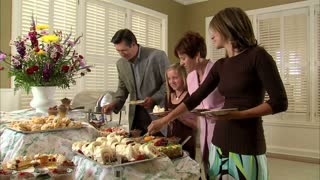 Family Puts Food on Plates at Buffet Table