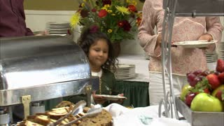 Family Puts Food on Their Plates at Buffet
