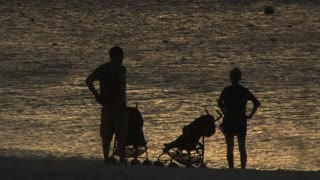 Family Silhouette Against Shimmering Ocean