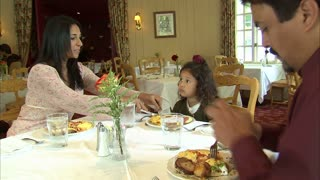 Family Sits Down to Eat a Meal at Restaurant
