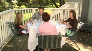 Family Sits Down to Eat Outside