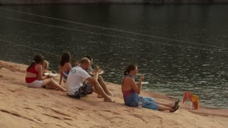 Family Sits On Red Rock Next To Houseboat On Lake