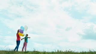Family turned and looking at the camera. Mother and daughter holding hands and looking at distance. Girl holding balloons. Zooming