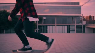 Fashionable rider in hipster red plaid shirt and black jeans just skates on longboard at twilight time with beautiful paster lightning, then stops and kicks out board to his hand, camera follows him