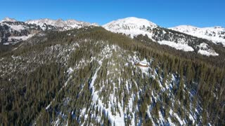 Fast flight forward over a remote snow covered cabin in the woods in mountains