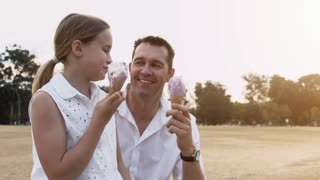 Father and Daughter eating ice cream at sunset in park, steadicam shot.