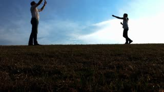 Father and daughter flying Kite on open field at sunset, steadicam shot.