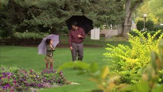 Father and Daughter Walking Under Umbrellas 2