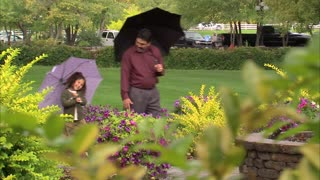 Father and Daughter Walking Under Umbrellas 3