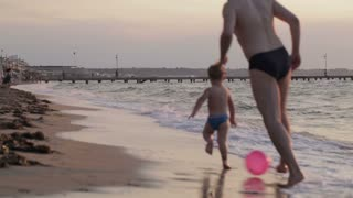Father and his little son running along the beach playing ball  in their swimsuits in evening light moving away from the camera along the sand at the edge of the surf