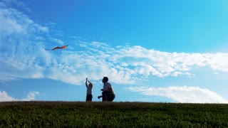 Father and son flying kite in open park with blue sky at sunset. Steadicam shot