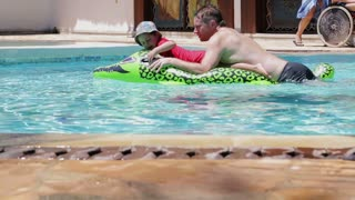 Father and son swimming together in the pool, steadycam shot