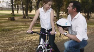 Father clipping helmet on daughters head before she starts to ride her bike. Steadicam shot.