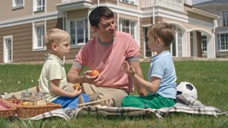 Father having picnic on green lawn with two little sons and smiling while one of them talking about something to him