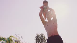 Father is playing with his baby daughter outdoors. Slow Motion 240 fps. Young dad and his cute little baby-girl are having fun in the sunny garden. Happy childhood and fatherhood concept. Young Family