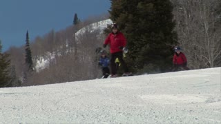 Father Leads Kids Down Ski Hill