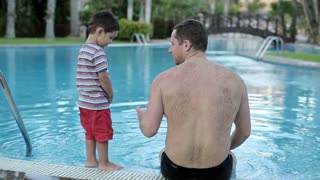 Father talking with his son by the poolside