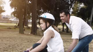 Father teaching daughter to ride her pink bike, steadicam shot.