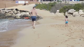 Father with his son running on the beach, slow motion shot at 240fps