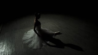 Female ballet dancer at a rehearsal on dark stage