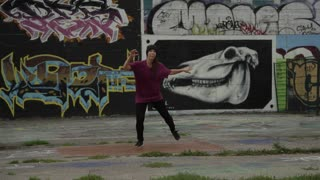 Female Break Dancer Performing in front of Graffiti Wall