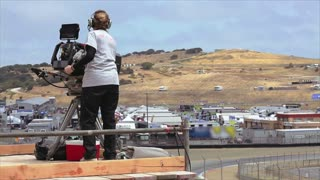 Female cameraman filming the racetrack in a f1 competition