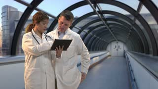 Female doctor explaining about patient with another doctor showing chart on clipboard. Shot in front of green screen; hospital background added afterwards. Identical green screen shot number 21243758