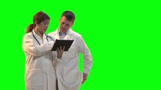 Female doctor explaining about patient with another doctor showing chart on clipboard. Shot in front of green screen. Identical shot with hospital background number 21243840