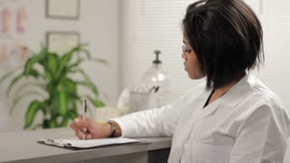 Female doctor writing, then looking at camera