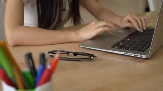 Female fingers with natural manicure on the keyboard laptop. On the wooden desk black glasses. Unrecognisable girl wearing in white shirt with short sleeves