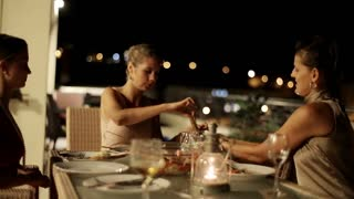 Female friends celebrating dinner on the terrace at night, steadycam shot