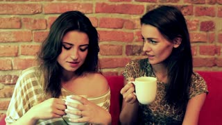 Female friends drinking coffee and smiling to the camera on the couch