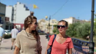 Female friends walking the street and talking