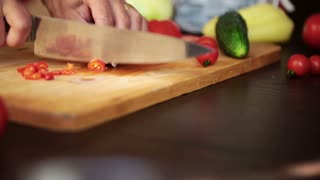 Female hands with knife, cutting fresh red chili peppers, steadicam