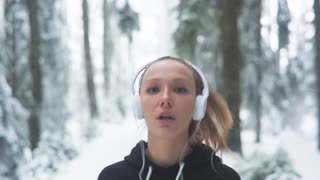Female Runner Jogging In Cold Winter Forest
