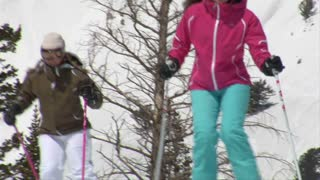 Female Skiers Glide Past Camera On Blue-sky Day
