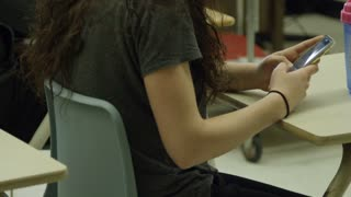 Female student in high school with smart phone sending messages